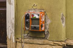 Old Broken Payphone. CLUJ-NAPOCA, ROMANIA - JULY 29, 2018: abandoned payphone on old rustic building in Cluj, Transylvania stock image