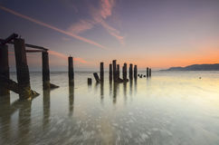 Old broken pier during awesome beatiful sunset. Vibrant colour. Royalty Free Stock Images