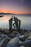 Old broken pier during awesoome beatiful sunset. Vibrant colour. Royalty Free Stock Photo