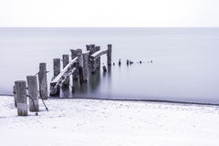 Old broken pier with rustic and weathered posts leading into a c Royalty Free Stock Photos