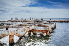 Old broken pier in the sea. Old broken concrete pier or jetty in the sea Stock Photo