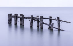 Old broken pier with weathered posts standing in tranquil calm s Stock Photography