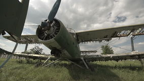 Old, broken plane on a green meadow shooting near. Shooting a broken plane in a military aircraft cemetery, among clouds on a green meadow stock video footage