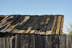 Old broken roof with rubber slabs, moss on the roof. Royalty Free Stock Photo