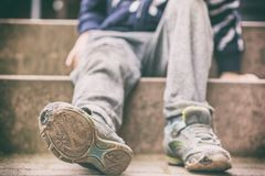 Old broken shoes of a little boy as a symbol for child poverty. Small unrecognizable boy sits on steps in worn out clothes and with tattered shoes stock photos
