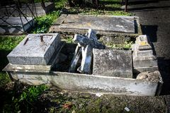 Old broken tomb in the cemetery. Detail of cross and broken old tomb of granite in the cemetery Stock Images