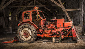 Old broken tractor. Antique red broken tractor in an old barn Royalty Free Stock Photo