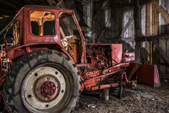 Old red tractor. Antique red broken tractor in an old barn of a former agricultural cooperative LPG in Eastern Germany Royalty Free Stock Photos