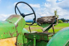 Old broken tractor seat on a farm. Shows the wheel and wood backing. Green and yellow old farm equipment. Broken tractor seat on a farm. Shows the wheel and wood royalty free stock image
