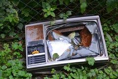 Old broken tv-set. Old broken television set discarded in woods Stock Image