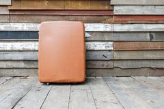 Old vintage brown suitcase on wooden wall. Old and broken vintage brown suitcase on wooden the  wall Royalty Free Stock Photos