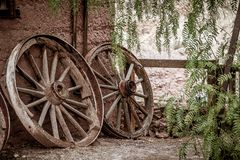 Old broken waggon wheels leaning against a wall Royalty Free Stock Photography