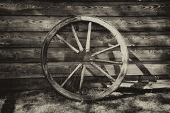 Old broken wagon wheel at the wall Stock Image