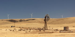 Old broken wind pump and new wind generators. Australia. Royalty Free Stock Photo