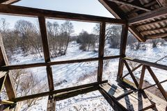 Old broken wooden balcony and the view of beautiful wild winter nature. Through it royalty free stock image