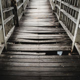 Old and broken wooden bridge. Old wooden bridge path across the lake/river to dead end,  selective focus Stock Photography