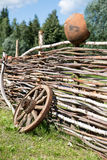 Old broken wooden carriage wheel on wattled fence Royalty Free Stock Images