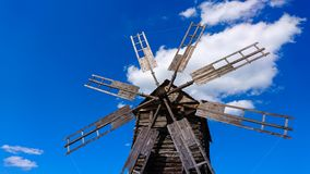 Old and broken wooden windmill against blue sky Royalty Free Stock Photos