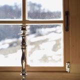 Old bronze candleholder. Against the window with wooden frame, interior closeup royalty free stock photo