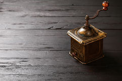 Old bronze coffee grinder on black wooden board Stock Photography