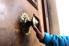 Old bronze door handle pushed by mans hand Royalty Free Stock Photography
