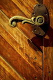 Old bronze handle on the wooden gate.  Royalty Free Stock Image