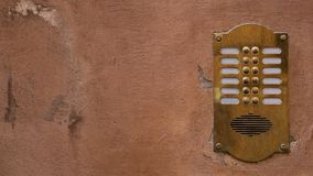 Old bronze intercom on an old wall with peeling paint. Ratio 16:9. Vintage background stock photos