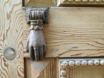 Old bronze knocker on a wooden door Stock Photos