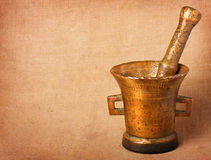 Old bronze mortar. And pestle on sacking background royalty free stock photo