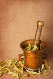 Old bronze mortar with herbs. Old bronze mortar with dry herbs on sacking background Royalty Free Stock Images