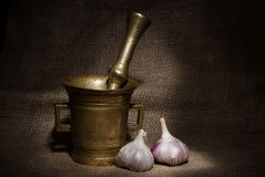 Old bronze mortar and pestle with garliс on canvas background Royalty Free Stock Photography