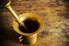 Old bronze mortar with pestle on wootden table Stock Photos