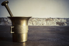 Old bronze mortar with pestle on wootden table Royalty Free Stock Photos