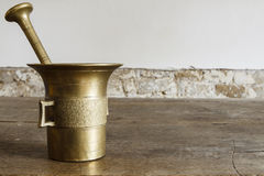 Old bronze mortar with pestle on wootden table Royalty Free Stock Images