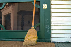 Old broom with hobo sign. On a green door of an old house royalty free stock photography