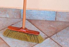 Old broom. Used broom laying against the wall Stock Photos