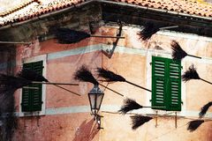 Old brooms put up above the street as decoration. The Old brooms put up above the street as decoration Stock Photography