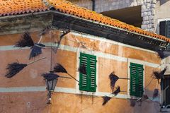 Old brooms put up above the street as decoration. The Old brooms put up above the street as decoration Stock Photos
