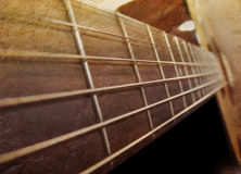Old Brown Acoustic Guitar Closeup. A closeup of an acoustic guitar strings going downward. The color uses a brown palette and there are dark shadows stock image