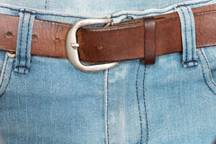 Old brown belt with blue jeans Royalty Free Stock Image