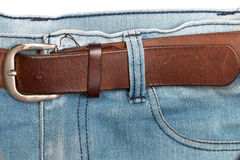 Old brown belt with blue jeans Royalty Free Stock Photos