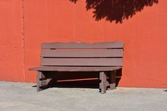 Old brown bench. Wooden brown painted bench against an orange painted wall stock photography