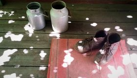 Old brown boots on red door mat and two vintage aluminum milk cans on wooden floor. Group of objects in sunspots Stock Photos