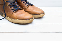 Old brown boots on a white wooden background Stock Images