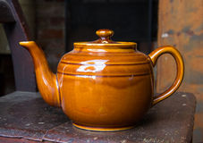 Old brown ceramic teapot on colored background Stock Photos