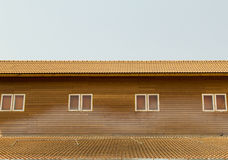 Old brown clay tiles roof pattern with small windows on wood wal Stock Photography