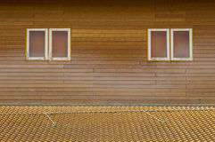 Old brown clay tiles roof pattern with small windows on wood wal Royalty Free Stock Photos