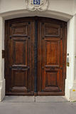 Old brown door with black handles Stock Photos