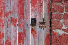 Old brown door handle and combination lock on wooden gray red door and humane fence boards. One old brown door handle and a combination lock on the wooden gray royalty free stock photo