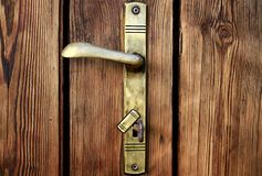 Old brown door with metal brass handles. Old door with metal brass handles with key no people stock photo royalty free stock image